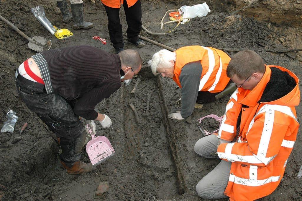 Het vrij leggen van een grafkist met menselijke resten