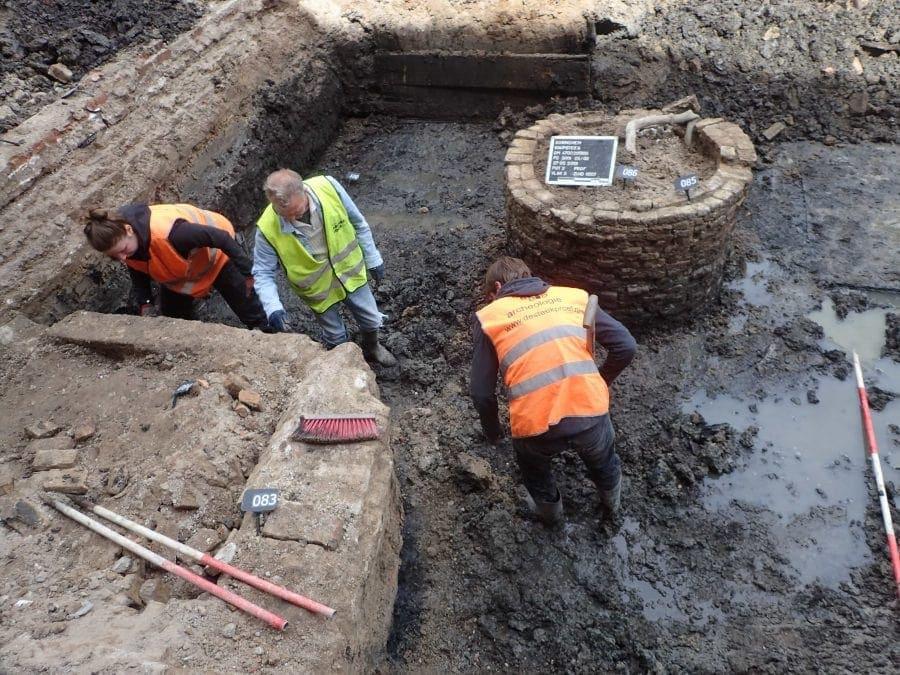 Middeleeuwse gracht met nog verrassend veel water, opgravingsterrein met in het midden een 19de eeuwse waterput.